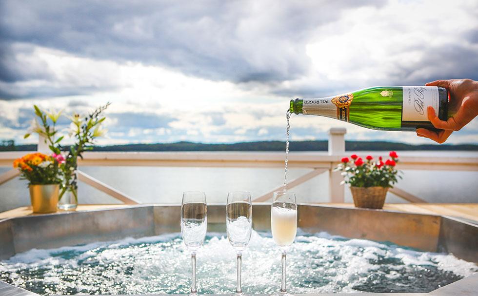 Häller upp champagne vid Spapoolen på bryggan på Krägga Herrgård